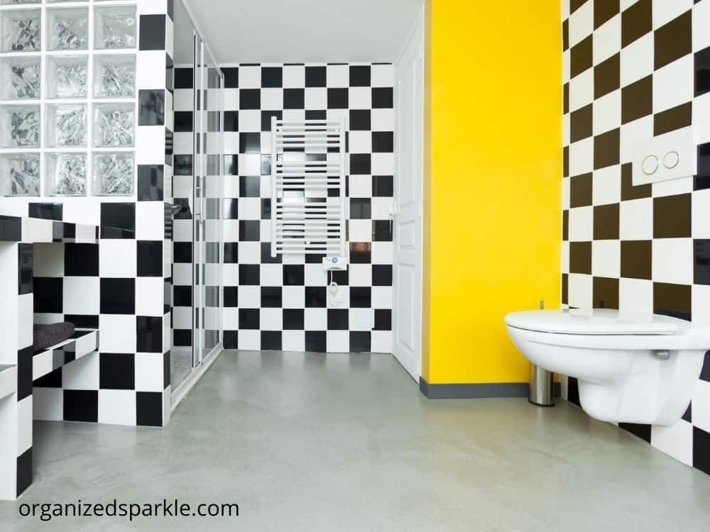bathroom with black and white check pattern tile flooring with yellow walls