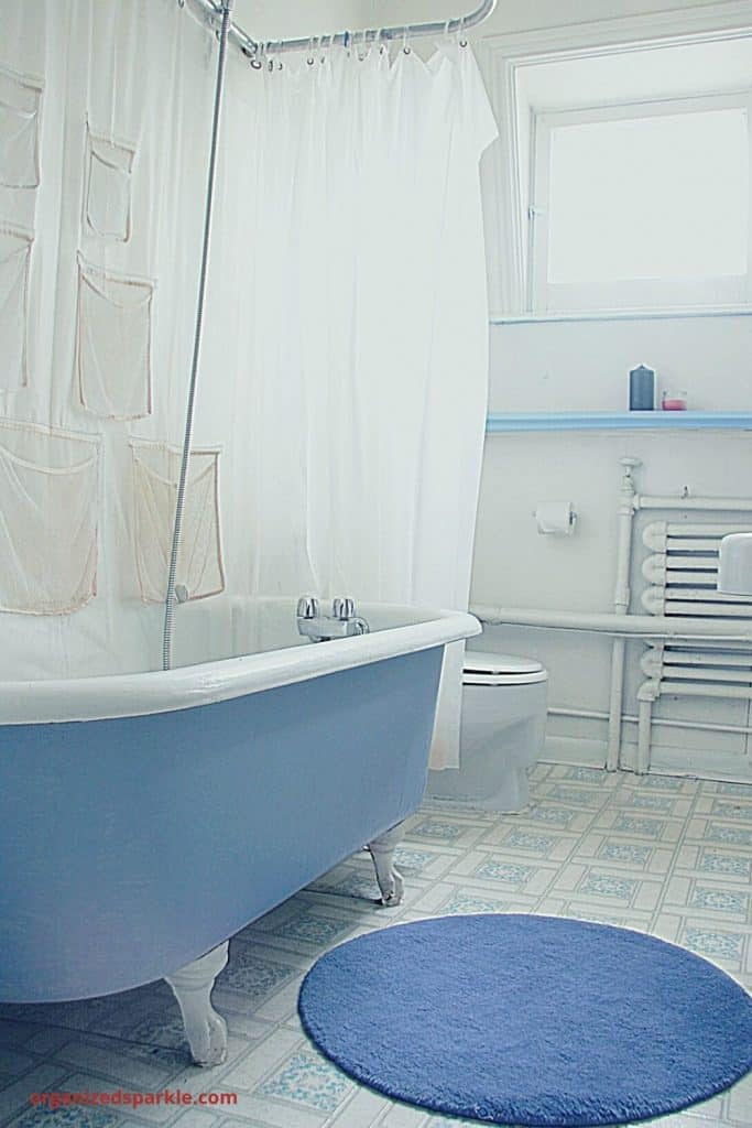 small blue and white bathroom with a clawfoot tub